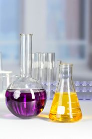 picture of beaker  - Laboratory flask and beaker with colored liquids over white table - JPG