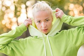 image of hoodie  - Portrait of attractive confident sporty woman wearing fashionable green hoodie while training in the nature - JPG