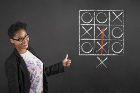 image of tic  - South African or African American black woman teacher or student with a thumbs up hand signal with tic tac toe standing against a chalk blackboard background inside - JPG