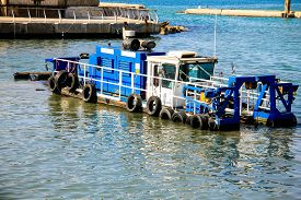 pic of dredge  - Dredge clears the waters of debris and excessive sand brought by the waves in the old port at Mediterranean sea - JPG