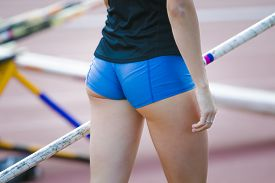 pic of competing  - A female athlete competing in the pole vault at a track and field event - JPG