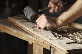 foto of chisel  - Closeup of a carpenter hands working with a chisel and hammer on wooden workbench - JPG