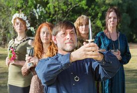 foto of priest  - Bearded pagan priest with group and holding ritual knife - JPG