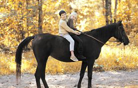 stock photo of horse girl  - Two children boy and girl riding on horse in autumn forest - JPG