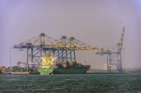 pic of shipyard  - Industrial container cargo freight ship with working crane bridge in shipyard - JPG
