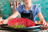Working in a butcher's shop - shop assistant with meat