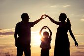 Happy Family Standing In The Park At The Sunset Time. poster