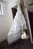 ruffled brides dress handing on the closet door