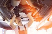 Mid adult automobile mechanic repairing car in workshop poster