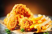 Fried chicken wings and legs with french fries on wooden table. Breaded Crispy fried kentucky chicke poster