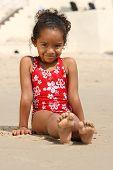 stock photo of children beach  - Cute little african american girl lying on a beach - JPG