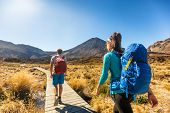 New Zealand Hiking Couple Backpackers Tramping At Tongariro National Park. Male and female hikers hi poster
