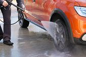 Man Washes His Orange Car At Car Wash. Cleaning With Water At Self-service Car Wash. Soapy Water Run poster