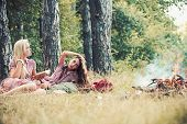 Women With Natural Makeup Relax On Green Grass. Beauty Girls With Long Hair At Bonfire. Fashion Wome poster