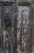 Ancient Wooden Door. Door Has Lovely Black Metal Patterned Clasp And Studded Pattern.  Shows Great T poster