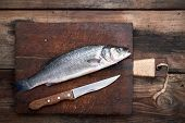Fresh Whole Sea Bass Fish On Brown Cutting Board And Knife , Top View poster