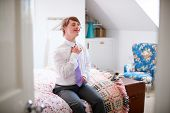 Young Downs Syndrome Man Sitting On Bed Getting Dressed For Work poster