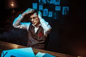 Pensive Detective Combing Hair With Comb In Dark Office poster