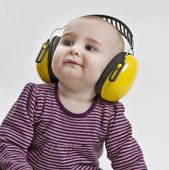 stock photo of noise pollution  - baby with yellow ear protection in loud environment - JPG