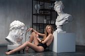 Young Woman Posing Among Ancient Greek God Apollo Bust Sculpture And Farnese Hercules Or Heracles He poster