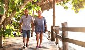 Happy Senior Couple Walking Holding Hand At Koh Phangan Beach Promenade - Active Elderly And Travel  poster