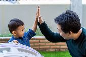 Asian Single Dad With Son Are Playing And Give Me Five Together When Living In Front Lawn For Self L poster