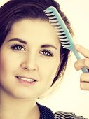 Woman Combing Her Healthy Hair Using Comb. Young Latin Female With Beautiful Natural Brown Straight  poster