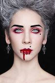 stock photo of marquise  - Portrait of young beautiful stylish gothic woman with vintage hairdo and bloody mouth - JPG