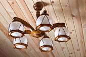 stock photo of flambeau  - beautiful wooden electric chandelier on wooden ceiling - JPG