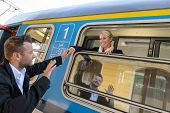 foto of say goodbye  - Man saying goodbye to woman on train smiling window commuter - JPG