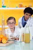 Постер, плакат: Дети проводит эксперимент на апельсины