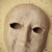 a simple paper-mache mask on a beige patterned background