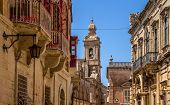 image of carmelite  - Street in Mdina full of balconies and the Carmelite convent in the end of the street - JPG