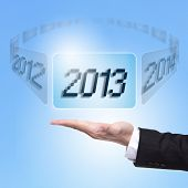 picture of chinese new year 2013  - hand of Business man holding screen button with 2013 number happy new year 2013 in business concept - JPG