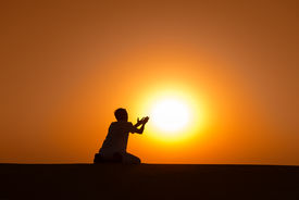 stock photo of emaciated  - Man silhouette kneel and pray for help with gold sunset sun on background - JPG