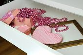 Gift box and beads in open desk drawer close up