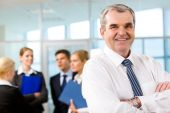 pic of young adult  - Image of senior leader smiling at camera in working environment - JPG