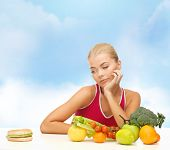 fitness, diet and food concept - doubting woman with fruits and hamburger
