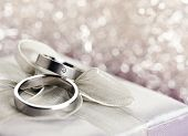 Pair of wedding rings on top of silver gift box with bow, bokeh in background, with copy space