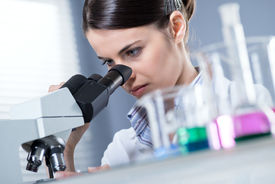 pic of beaker  - Young female researcher using microscope in the chemistry lab with laboratory glassware on foreground - JPG
