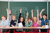 picture of youngster  - Enthusiastic group of young kids in class sitting in a row at their desk raising their hands in the air to show the know the answer to a question - JPG