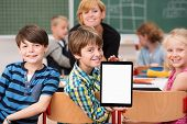 picture of presenter  - Little boy presenting a blank tablet in class turning in his chair to show it to the camera watched by smiling classmates - JPG