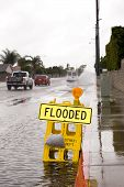 stock photo of hydroplanes  - A car kicks up a pool of rainwater over a street floded sign during bad rainy weather - JPG