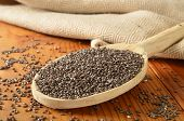 foto of tablespoon  - Organic chia seeds in a wooden spoon. Shallow depth of field focus in center area of spoon