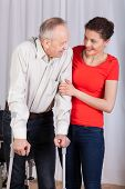 stock photo of crutch  - Senior walking with crutches insured by physiotherapist - JPG