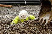 stock photo of track-hoe  - Worker using a small tracked excavator to dig a hole to fix a water leak at a large commercial housing development in Oregon - JPG