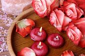 foto of unity candle  - Spa concept with roses pink salt and candles that float in a wooden bowl with water top view - JPG
