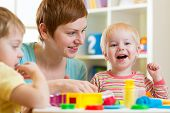 foto of daycare  - mother and her children have fun with colorful play clay toys - JPG
