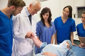 stock photo of professor  - Medical students and professor checking pulse of student at the university - JPG