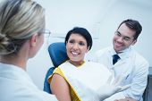 stock photo of dentist  - Portrait of smiling male dentist and assistant with female patient in the dentists chair - JPG